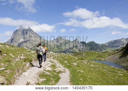 Two Hiker In Front Of The Midi D'ossau And In The Ayous Lakes, Pyrenees, France
