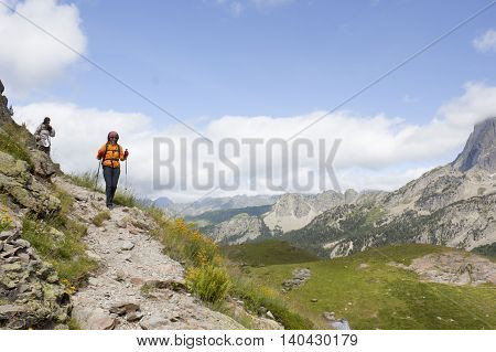Two Mountaineers Hiking In The High Of A Mountain In The Pyrenees, France