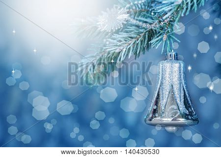 Holiday card. Toy in the shape of a bell hanging on a branch of a snow-covered spruce