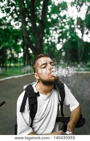 Man with beard and smoke. Thick steam. Bicycle. Vape.