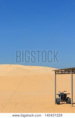 motor quad in desert - white sand dune