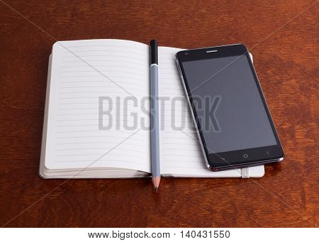 Opened notebook with a pencil and a smartphone brown surface