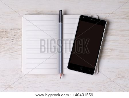 Opened notebook with a pencil and a cell phone on white wooden surface