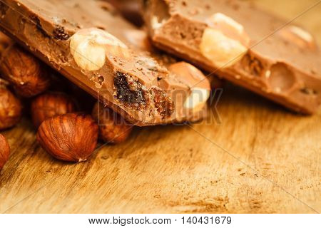 Sweet food. Closeup milk chocolate pieces and hazelnuts on wooden table.