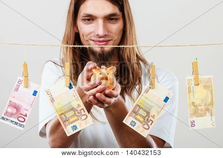 Savings concept. Young handsome long haired joful man holding piggybank moneybox around banknotes cash.