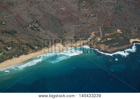 Aerial of Northwest coast of Molokai with waves crashing into Sandy Beach and surrounding area of island with roads largely undeveloped. April 2016.