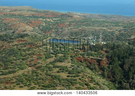 Aerial of countryside running to the ocean with Water reservoir and communications towers on Molokai largely undeveloped with trees and bushes. April 2016.