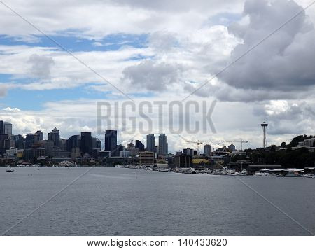 Cranes and skyscrapers line Seattle Skyline Wa USA. Boats in the forground and clouds in the sky. June 2016.