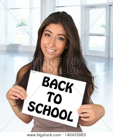 Beautiful young woman holding a back to school sign.
