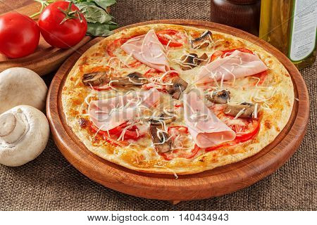 Pizza with ham, mushrooms, tomatoes pepper and mozzarella