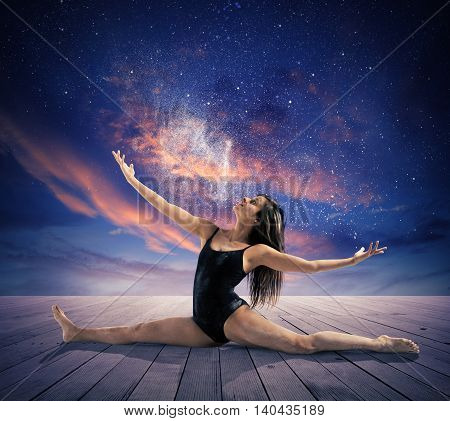 Dancer makes a split under the stars in the sky