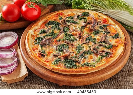 Pizza with anchovies, spinach, tomatoes and cheese