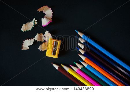 Colored pencils, sharpener and shavings on a black background