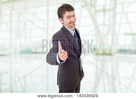 young man in suit offering to shake the hand, at the office
