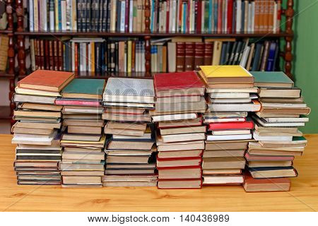 Large Pile of Books With Library Shelf in the Background