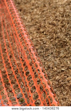 Construction safety fence with wood chips in the background