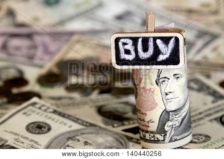 Buy sign with a background of American dollars.