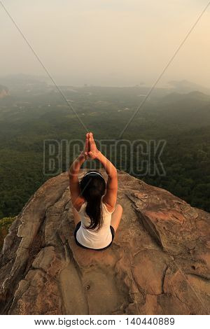 one young yoga woman at mountain peak