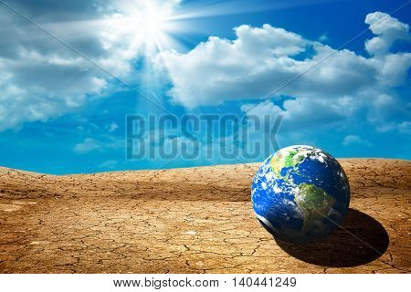 conceptual image of globe on dry cracked landscape. Furnished NASA image used for this image