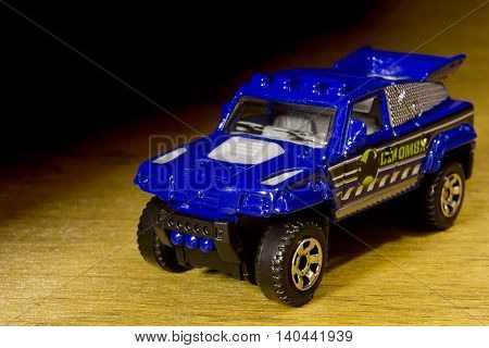 Blue toy car SUV on the wooden table
