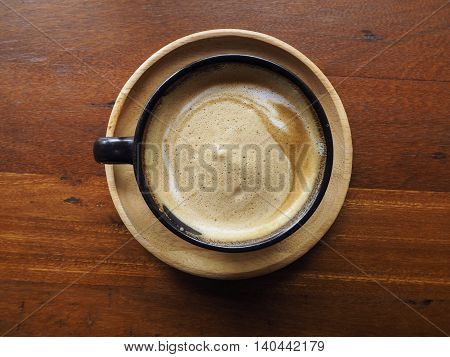 Hot cappuccino coffee in black cup for wood background.