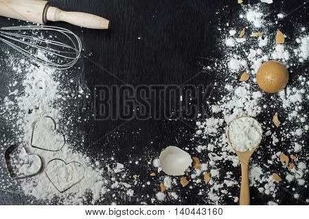 heart of flour in wooden spoon whisk rolling pin and eggshell on wooden table for baking background