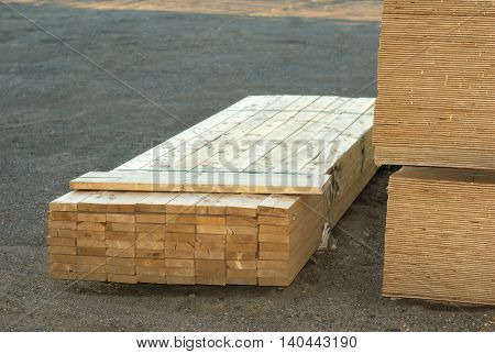 wood planks stacked on construction site with boards
