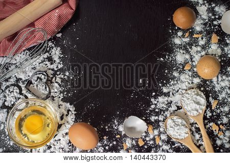 heart of flour flour in wooden spoon whisk rolling pin and eggshell on wooden table for baking background