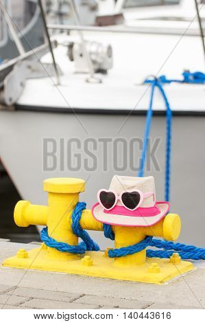 Straw hat and sunglasses in port with yacht in background travel and vacation time sun protection on summer