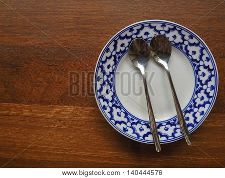 Blue flower clay plate and twin spoon on wooden floor.
