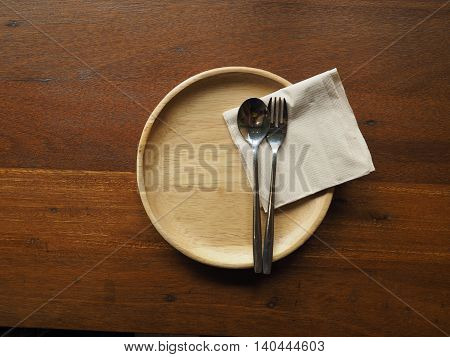 Simple dinner set in restaurant. Fork and spoon on wood disk for wooden table.
