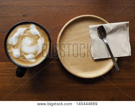 Coffee tree time in restaurant. Hot cappuccino in black cup for wooden table.