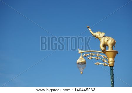 Sculpture of lanterns and golden statues of elephants with blue sky background in the public park Chonburi Province Thailand.