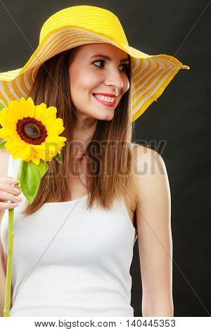 Portrait of attractive summer woman in yellow hat with sunflower in hand on black background