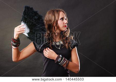 Portrait of beautiful brunette woman with black feather fan in hand