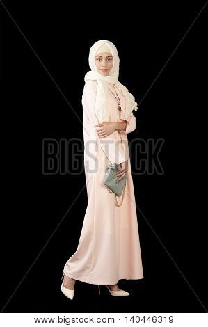 Studio photo of the girl of Middle Eastern appearance in the bright closed modern Muslim dress high heels on a black background Tatarstan