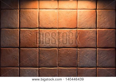 Texture of fine ceramic tiles for kitchen wall illuminated from above. Close up of tiled wall for background.