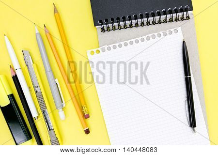 Office Supplies, Notebook And Squared Piece Of Paper On Yellow Desk Background