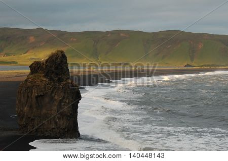 rock protruding from sand near ocean water with lush green mountain