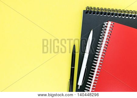 Red And Black Notebooks And Ballpoint Pens On Yellow Background