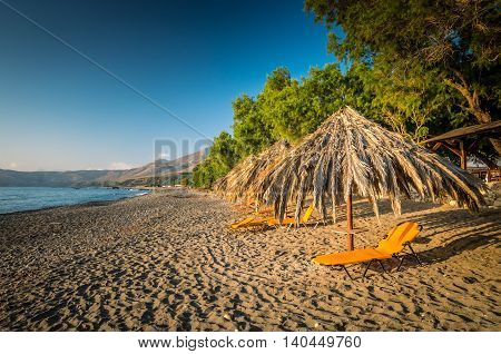 Sfinari Beach in Crete island, Greece. Straw parasols and sunbeds on the beach in twilight.