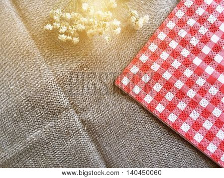 Red and white napkin and small flowers on burlap tablecloth