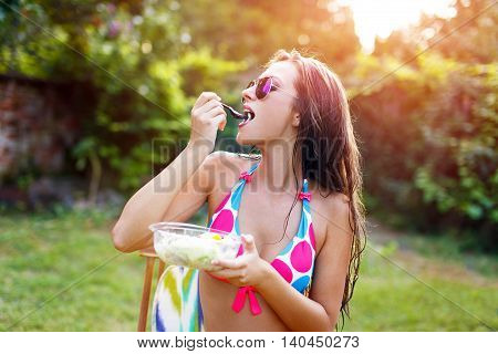 Healthy lifestyle woman in bikini eating salad outdoors in sunset. Young female eating healthy food outside in bikini side view.