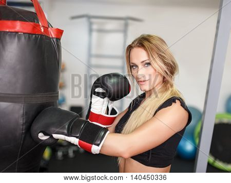 Blonde kickboxer woman punching into heavy bag