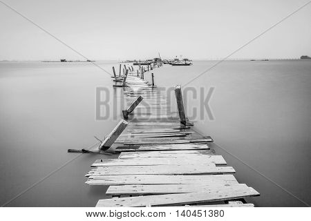 Water overflow on a broken wooden bridge in black and white