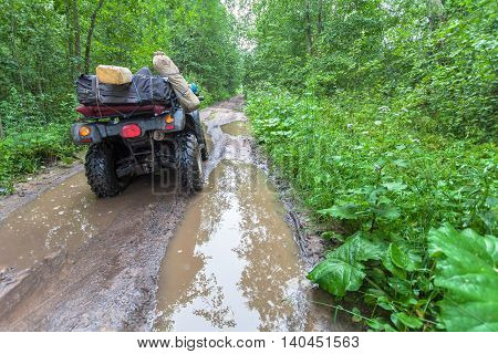 Dirty ATV stands with bags and stuff in the deep muddy puddle on the forest road