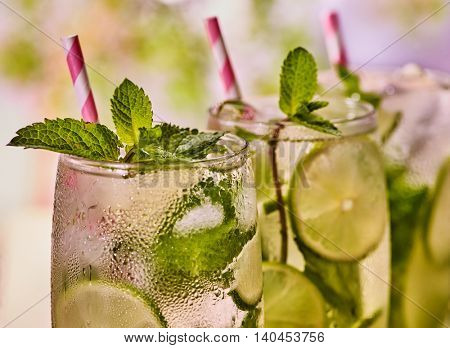 Alcohol drink. On wooden boards three high glasses with alcohol drink and ice cubes. Drink number two hundred ninety-five cocktail mohito with mint leaf sprig . Country life. Light background.