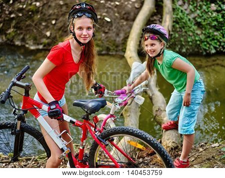Children girl with bicycle. Girls rides bicycle. Girls sister cycling fording throught water on log. Cycling trip is good for health. Cyclist watch at camera down up.