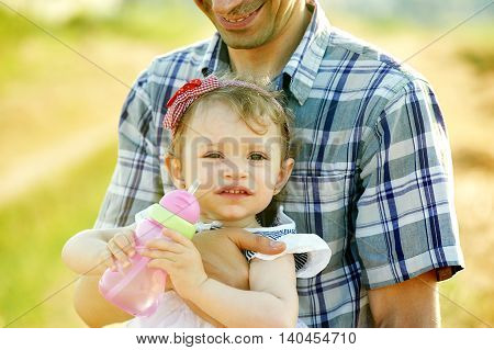 The little girl at the hands of the father , close-up