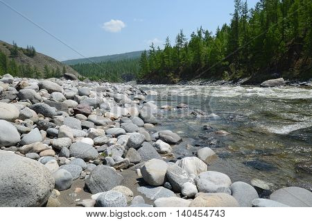 Rocky shore of Irkut River in its beginning in the Sayan Mountains in summer day